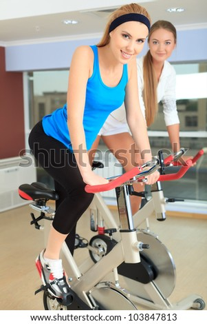 Young sporty women doing exercises on bicycles in the gym centre. - stock photo