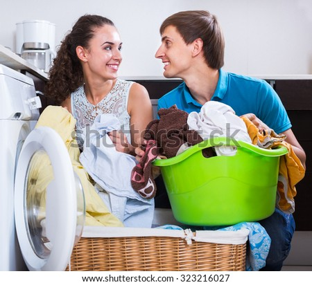 Young spouses doing  laundry and smiling at home - stock photo