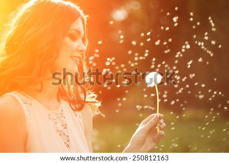Young spring fashion woman blowing dandelion in spring garden. Springtime. Trendy girl at sunset in spring landscape background. Allergic to pollen of flowers. Spring allergy  - stock photo