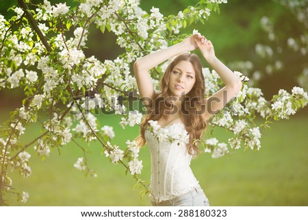 Young spring fashion woman in spring garden Springtime Summertime Trendy girl in the flowering trees in then at sunset in spring  summer landscape background Allergic to pollen of flowers Allergy  - stock photo