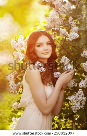 Young spring fashion woman  in spring garden. Springtime. Trendy girl at sunset in spring landscape background. Allergic to pollen of flowers. Spring allergy  - stock photo