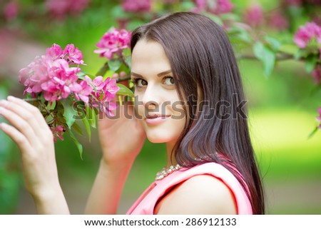 Young spring fashion woman. Trendy girl in the flowering trees in the spring summer garden. Springtime or summertime. Lady in spring landscape background. Allergic to pollen of flowers Spring allergy  - stock photo