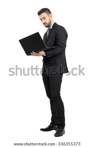 Young standing business man working on a laptop. Full body length portrait isolated over white studio background.  - stock photo
