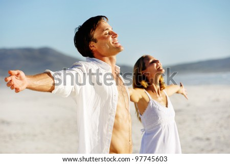 Young stress free couple enjoy the summer sun on the beach. Arms out, heads back and carefree attitudes. - stock photo
