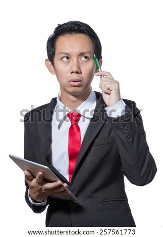 Young Stressed business man holding tablet and pen and thinking - stock photo