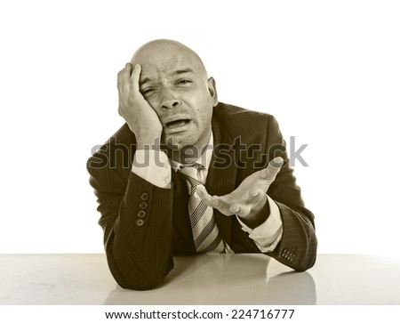 Young stressed businessman in suit and tie sitting on desk desperate crying and collapsed in financial crisis and work problems isolated on white background black and white studio - stock photo