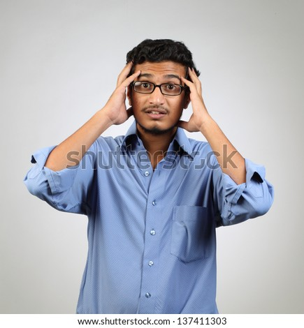 Young stressed man with hand on his face - stock photo