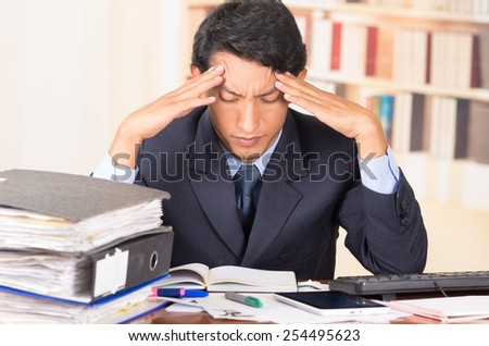 young stressed overwhelmed business man holding head with his hands looking at piles of folders on his desk - stock photo