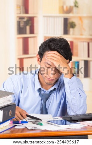 young stressed overwhelmed business man with piles of folders on his desk - stock photo