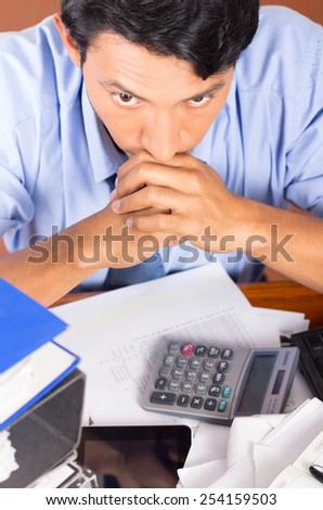 young stressed overwhelmed business man with piles of folders on his desk top view - stock photo