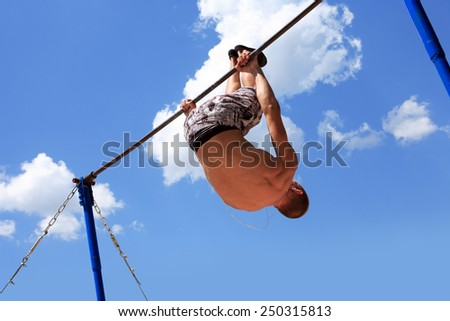 Young strong athlete doing exercise on horizontal bar against blue sky - stock photo