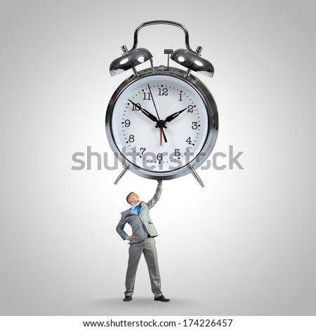 Young strong businessman lifting huge alarm clock above head - stock photo