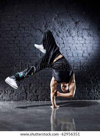 Young strong man break dance. On dark wall background. - stock photo