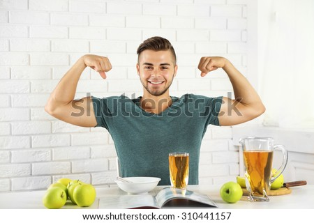 Young strong man having light breakfast  - stock photo