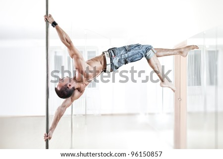 Young strong pole dance man. - stock photo