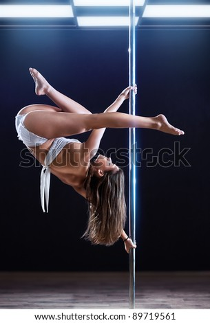 Young strong pole dance woman. - stock photo