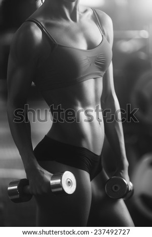 Young strong woman black and white portrait. Brunette sexy fitness girl in sport wear with perfect body in the gym posing before training set. Attractive fitness woman, trained female body - stock photo