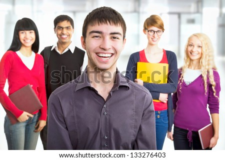 Young student and his diversity friends on background - stock photo