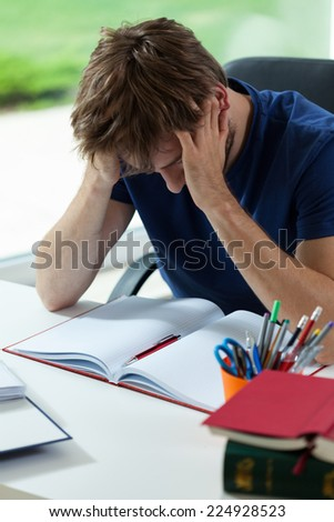 Young student depressed and tired before hard examination - stock photo
