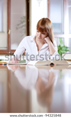 Young student doing her homework at a table - stock photo