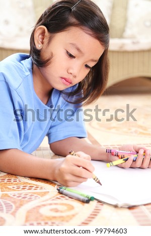 young student drawing with crayons. - stock photo