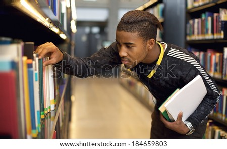 Young student finding reference books in university library. Finding information for his studies. - stock photo