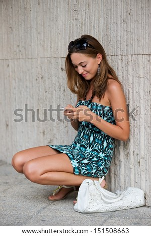 Young Student Girl (21) Browsing The Internet With Her Cell Phone in Urban Environment - stock photo