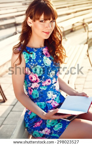 young student girl reading in the park - stock photo