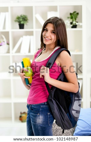 Young student girl ready for school, holding books and book bag - stock photo