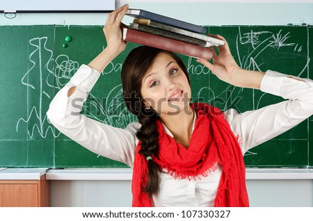 Young student girl with her books at blackboard background - stock photo