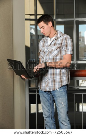Young Student holding a Laptop computer inside a College Building - stock photo