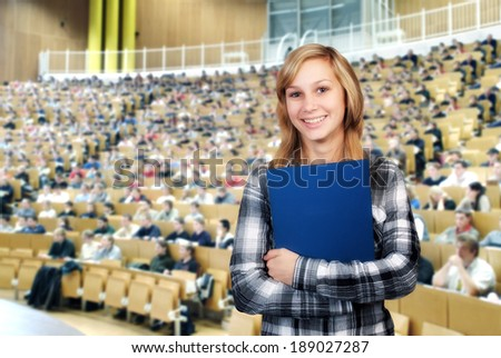 Young student in front of the auditorium in a large lecture hall. - stock photo