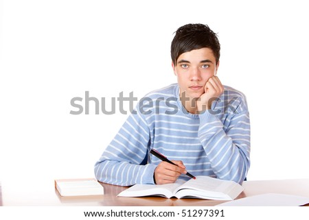 Young student is sitting on desk with open book and learns for his exams. He looks neutral into camera. Isolated on white. - stock photo