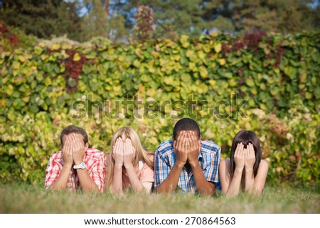 Young student lay in park on grass and close their faces with  hands in park - stock photo