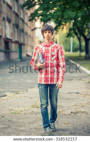 young student man holding a book and tablet against a city background - stock photo
