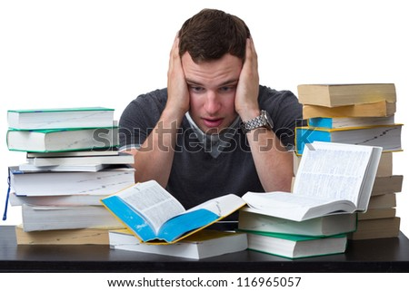 Young Student overwhelmed with studying with piles of books in front of him - stock photo