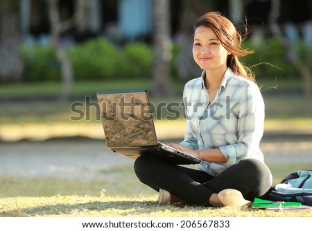 Young student sitting cross-legged on grass with laptop doing a homework - stock photo
