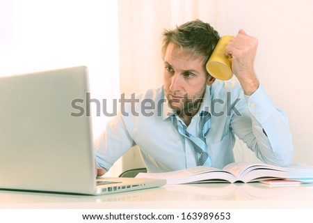 Young Student Stressed and Overwhelmed working on Laptop holding a cup of Coffee - stock photo