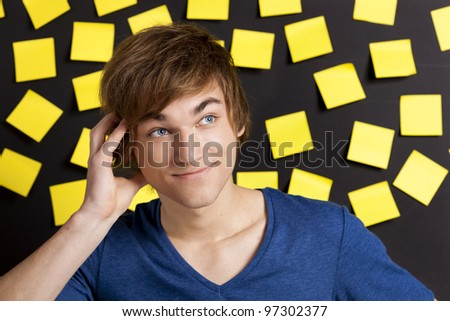 Young student thinking in front of a board full of  yellow notes - stock photo
