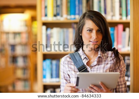 Young student using a tablet computer in the library - stock photo