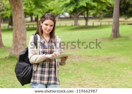 Young student using a tactile tablet in a park - stock photo