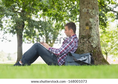 Young student using his laptop to study outside on college campus - stock photo