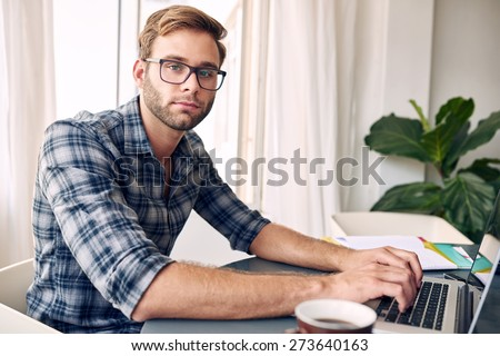 Young student wearing a check shirt and glasses looks into camera while typing on his new notebook, with a cup of coffee on the ready and files on his desk - stock photo