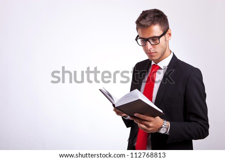 young student wearing glasses and reading a law book on grey background - stock photo