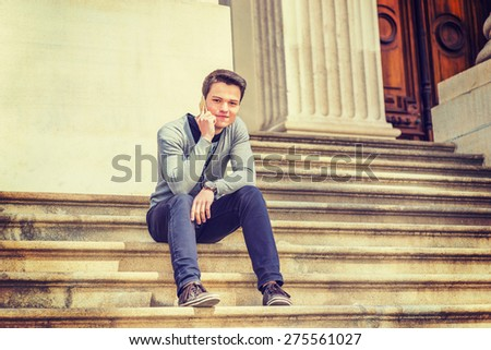 Young Student. Wearing gray V neck cardigan sweater, blue pants, brown sneaker, wristwatch, a young guy sitting on stairs outside office building, smiling, making phone call. Instagram effect.  - stock photo