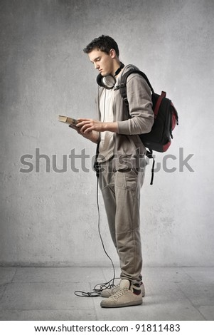 Young student wearing headphones and holding a book - stock photo