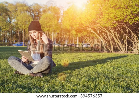 Young Student Woman Hipster Style sitting outdoor with tablet pc, listening music and communicate with friends through social network   - stock photo