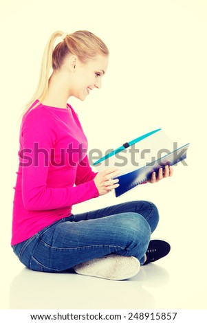 Young student woman sitting cross legged with workbook. - stock photo