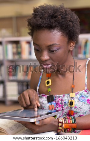Young student working on her assingment Tablet - stock photo