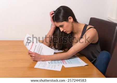 young student worried over un-paid bills and student loan - stock photo